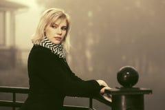 Junge Modefrau im schwarzen Mantel, der auf dem Handlauf im Freien sich lehnt Lizenzfreies Stockfoto