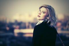 Junge Modefrau im schwarzen Mantel gehend auf Stadtstraße Lizenzfreie Stockbilder