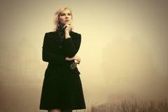 Junge Modefrau im schwarzen Mantel gehend in einen Nebel im Freien Lizenzfreies Stockbild