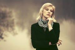 Junge Modefrau im schwarzen Mantel gehend in einen Nebel im Freien Lizenzfreies Stockfoto