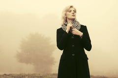 Junge Modefrau im schwarzen Mantel gehend in einen Nebel im Freien Lizenzfreie Stockfotos