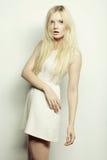 Junge Modefrau im weißen Kleid, das im Studio aufwirft Lizenzfreies Stockfoto