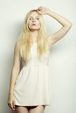 Junge Modefrau im weißen Kleid, das im Studio aufwirft Stockfotos