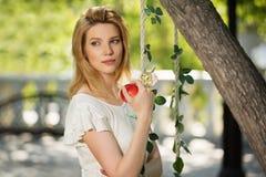 Junge Modefrau mit Apfel in einem Stadtpark Lizenzfreie Stockfotos