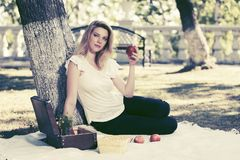 Junge Modefrau mit Apfel im Stadtpark Stockbild