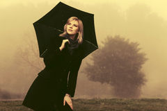 Junge Modefrau mit dem Regenschirmgehen im Freien Lizenzfreie Stockfotografie