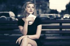 Junge Modefrau mit dem Tablet-Computer, der auf Bank sitzt Lizenzfreie Stockfotografie