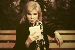 Junge Modefrau mit dem Tablet-Computer, der auf Bank sitzt Lizenzfreie Stockbilder