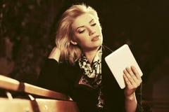 Junge Modefrau mit dem Tablet-Computer, der auf Bank sitzt Stockfoto