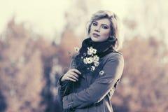 Junge Modefrau mit einem Blumengehen im Freien Stockbild