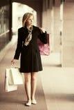 Junge Modefrau mit Einkaufstaschen gehend in das Mall Lizenzfreie Stockfotos