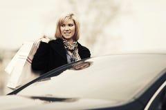 Junge Modefrau mit Einkaufstaschen nahe bei Auto Lizenzfreie Stockfotos
