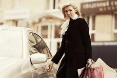 Junge Modefrau mit Einkaufstaschen nahe bei ihrem Auto Lizenzfreie Stockbilder