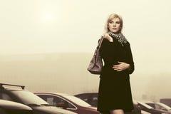 Junge Modefrau mit Handtasche in einer Stadtstraße Lizenzfreies Stockfoto