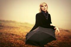 Junge Modefrau mit Regenschirm in einem Nebel im Freien Stockfoto
