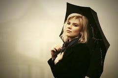 Junge Modefrau mit Regenschirm gehend in einen Nebel im Freien Stockfotografie