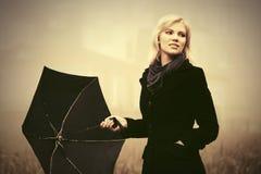 Junge Modefrau mit Regenschirm gehend in einen Nebel im Freien Stockfotos