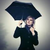 Junge Modefrau mit Regenschirm gehend in einen Nebel im Freien Stockfoto