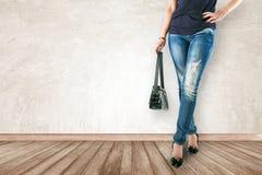 Junge Modefrau ` s Beine in den Jeans und halten Tasche auf hölzernem Florida lizenzfreie stockfotografie