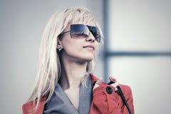 Junge ModeGeschäftsfrau in der Sonnenbrille gehend in eine Straße Lizenzfreie Stockfotos