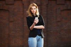 Junge ModeGeschäftsfrau, die intelligentes Telefon verwendet Stockbilder