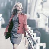 Junge ModeGeschäftsfrau, die in Stadtstraße geht Stockfotografie