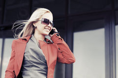 Junge ModeGeschäftsfrau, die um den Handy ersucht Lizenzfreie Stockfotografie