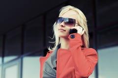 Junge ModeGeschäftsfrau, die um den Handy ersucht Lizenzfreies Stockfoto
