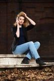 Junge ModeGeschäftsfrau, die um den Handy im Freien ersucht Stockfoto