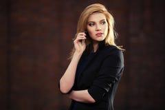 Junge ModeGeschäftsfrau, die um den Handy im Freien ersucht Stockfotografie