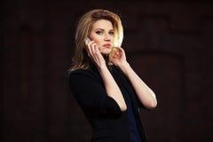 Junge ModeGeschäftsfrau, die um den Handy im Freien ersucht Lizenzfreie Stockbilder