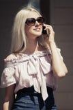 Junge ModeGeschäftsfrau, die um Handy ersucht Stockbilder