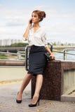 Junge ModeGeschäftsfrau, die um Handy ersucht Lizenzfreie Stockbilder