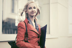 Junge ModeGeschäftsfrau mit einem Ordner am Bürogebäude Stockfotos