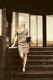 Junge ModeGeschäftsfrau mit Handtasche auf den Schritten am Bürogebäude Stockfotos