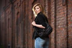 Junge ModeGeschäftsfrau mit Handtasche gehend auf Stadtstraße Stockfotografie