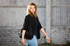 Junge ModeGeschäftsfrau mit Handtasche gehend in Stadtstraße Lizenzfreie Stockbilder