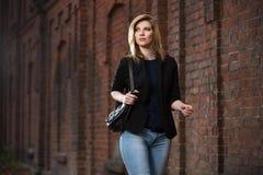 Junge ModeGeschäftsfrau mit Handtasche gehend in Stadtstraße Stockfotografie