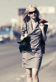 Junge ModeGeschäftsfrau mit Handtasche gehend in Stadtstraße Lizenzfreies Stockfoto