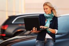 Junge ModeGeschäftsfrau mit Laptop durch ihr Auto Stockfotografie