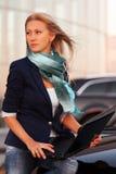Junge ModeGeschäftsfrau mit Laptop durch ihr Auto Stockbilder