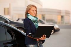 Junge ModeGeschäftsfrau mit Laptop durch ihr Auto Lizenzfreie Stockfotos
