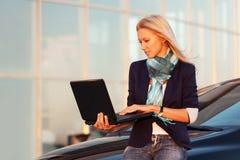 Junge ModeGeschäftsfrau mit Laptop durch ihr Auto Lizenzfreies Stockfoto