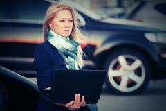 Junge ModeGeschäftsfrau mit Laptop nahe bei ihrem Auto Stockfotos