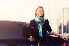 Junge ModeGeschäftsfrau mit Laptop nahe bei ihrem Auto Stockbilder