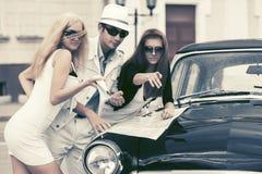 Junge Modeleute mit einer Straßenkarte durch Weinleseauto Stockbild