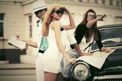 Junge Modeleute mit einer Straßenkarte nahe bei Weinleseauto Lizenzfreie Stockbilder
