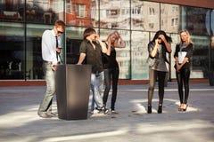 Junge Modeleute, welche um die Handys ersuchen Stockbilder
