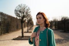 Junge Modeliebhaberfrau, die in einem Park trägt klare grüne Jacke und einen bunten Rock waling ist lizenzfreie stockfotografie