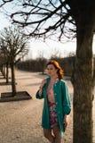Junge Modeliebhaberfrau, die in einem Park trägt klare grüne Jacke und einen bunten Rock waling ist lizenzfreies stockfoto